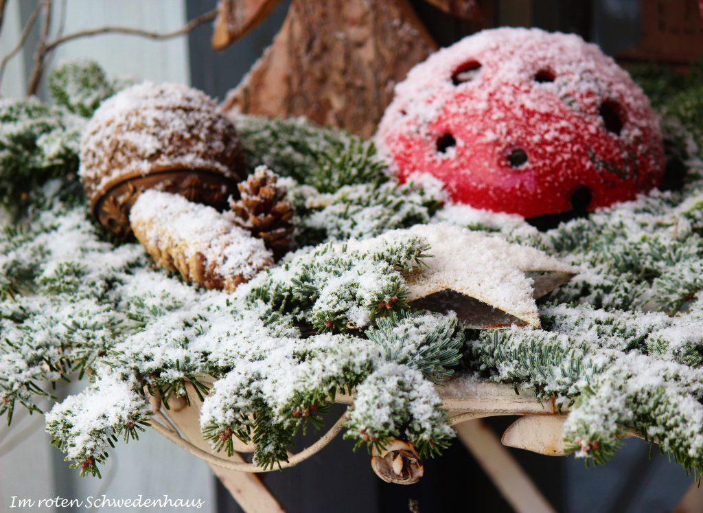 Tannenzapfen und Kugel im Schnee überzuckert.