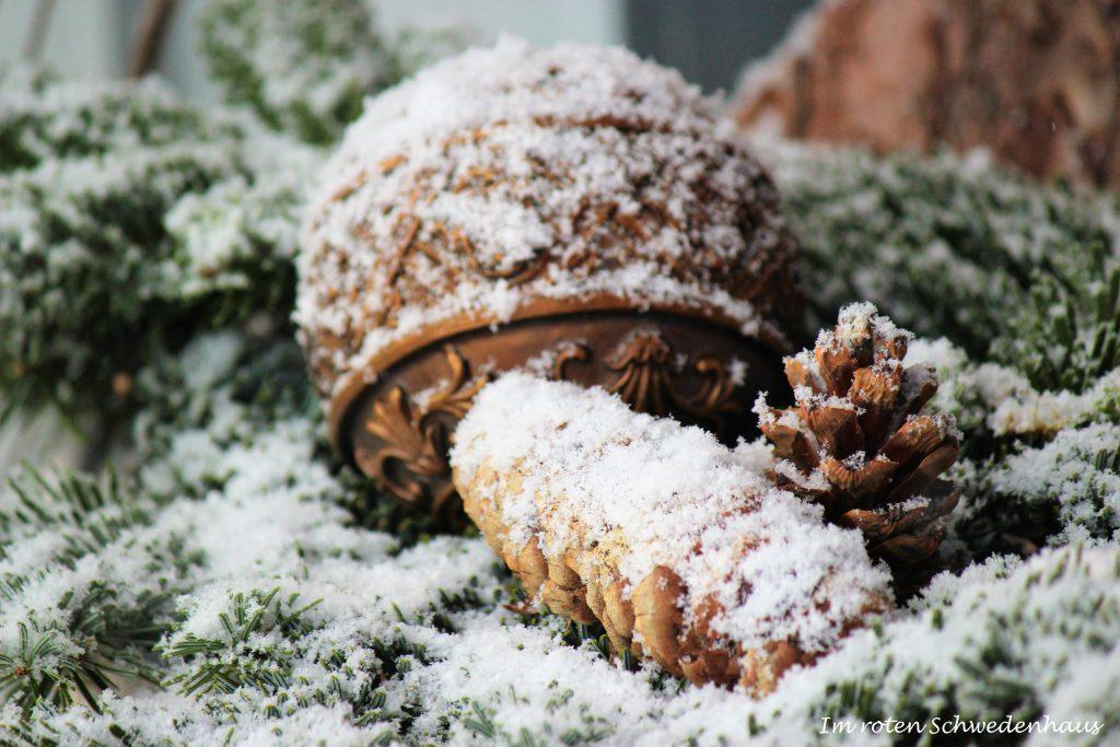 Tannenzapfen und Kugel im Schnee.