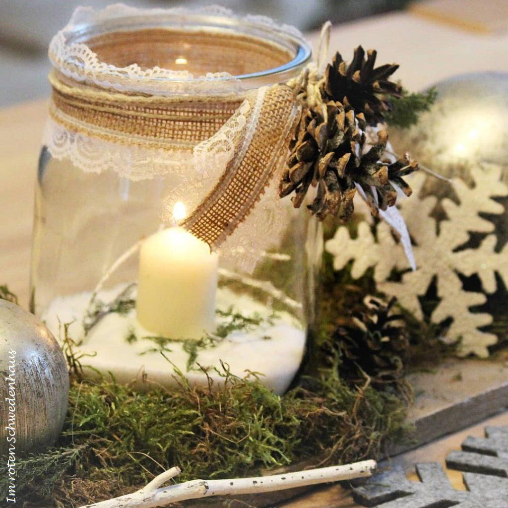 Winterliches Windlicht drapiert auf einem Dekobrett zusammen mit Naturmaterialien.