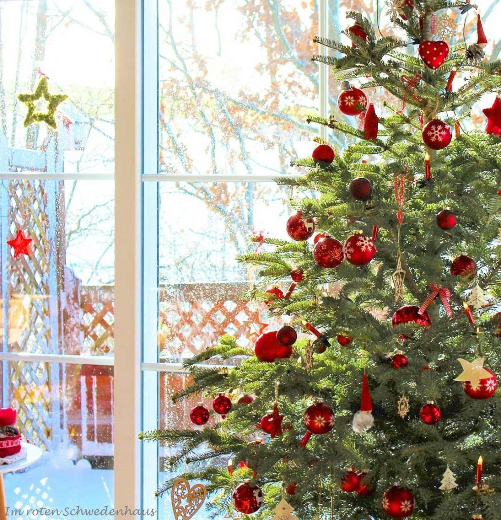 Weihnachtsbaum vor großem Fenster geschmückt in klassischem Rot