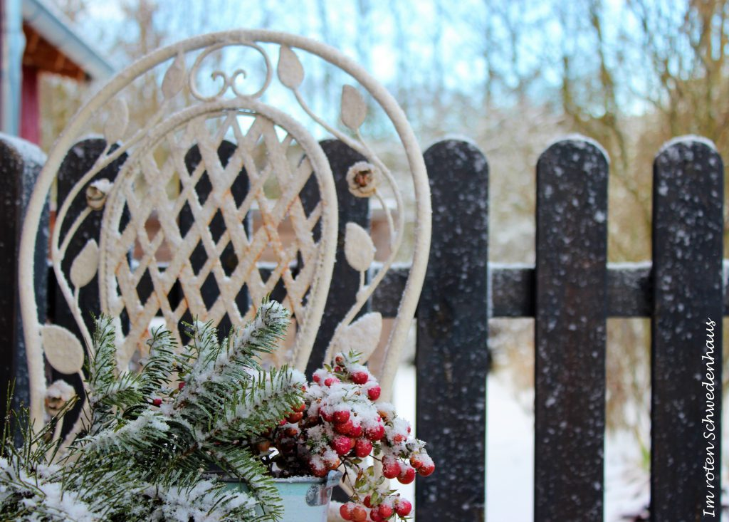Schneegestöber mit roten Beeren auf Stuhl.