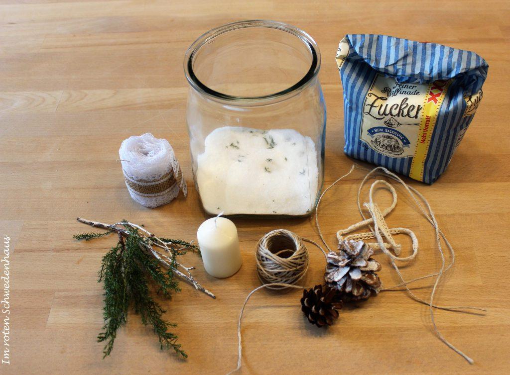 Bastelutensilien für ein winterliches Windlicht: Vase, weiße Kerze, Jute- oder Spitzenband, Paketschnur, zwei Zapfen, Tannenzweig, Kunstschnee oder Zucker