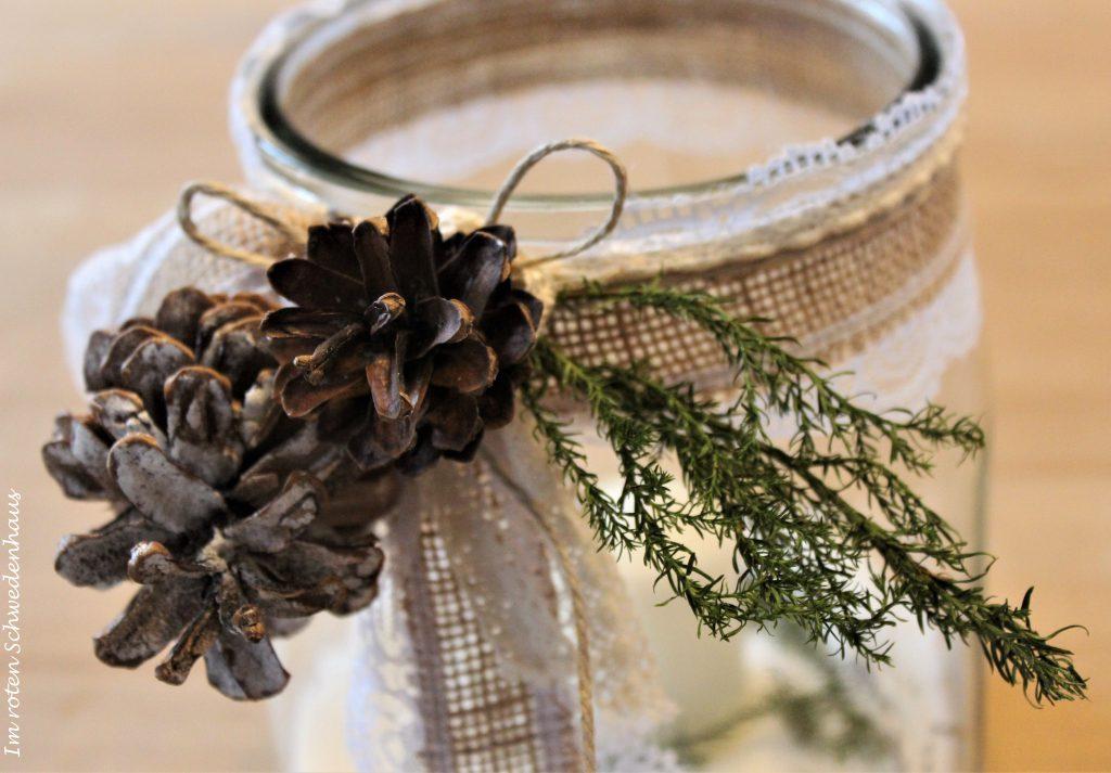 Winterliches Windlicht mit Juteband, Zapfen und Tannenzweig dekoriert.