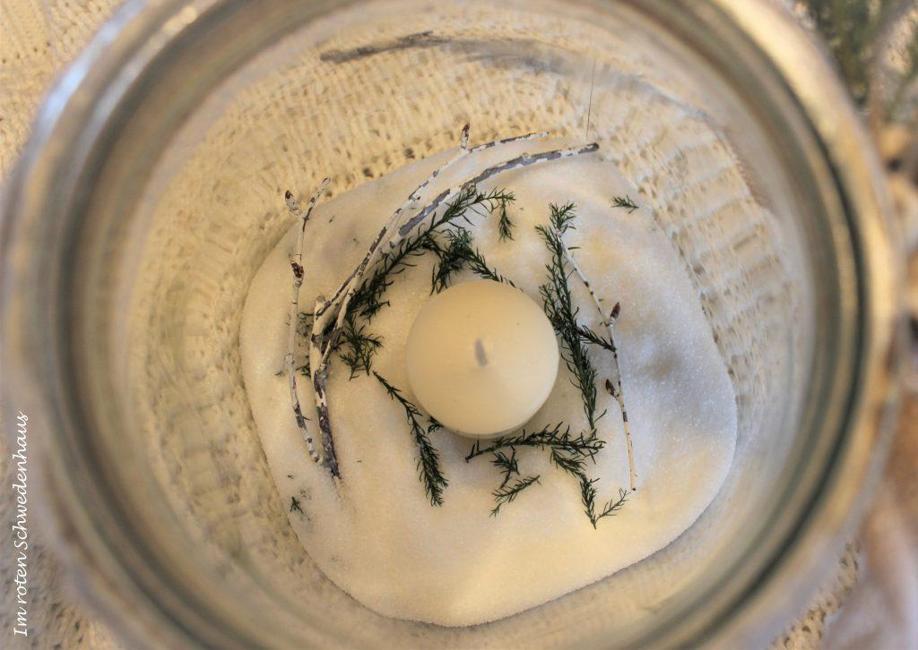 Blick von oben in die Vase mit Zucker, Kerze und Tannennadeln.