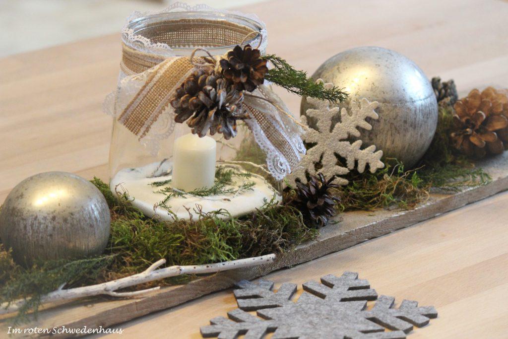 Ein altes Schalungsbrett auf dem Esstisch dekoriert mit winterlichem Windlicht, Kugeln aus Bauernsilber, Zapfen, Moos und einer Schneeflocke.