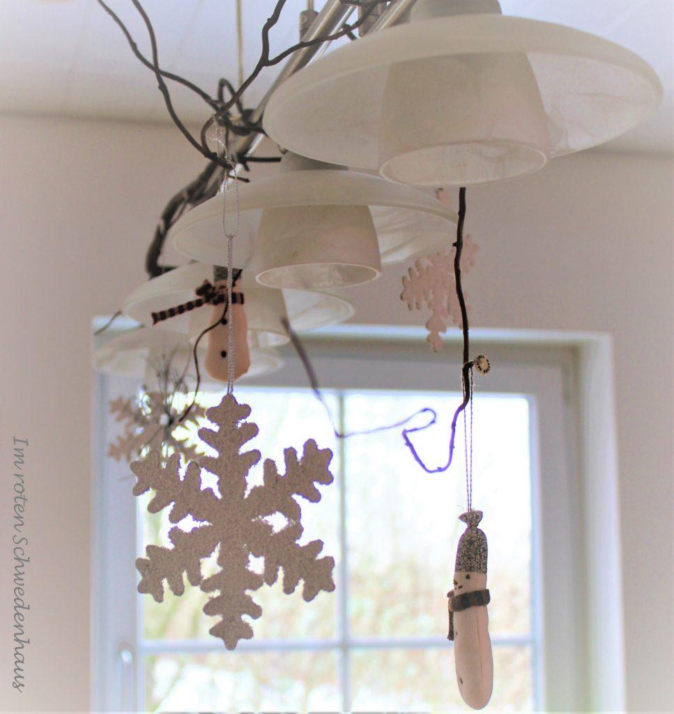 Schneeflocken und Schneemänner aus Stoff am Ast einer Korkenzieherhasel, der an einer Lampe befestigt ist.