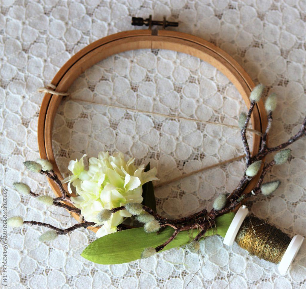 Am Stickrahmen sind nun Zweige und Blumen mit Draht befestigt.