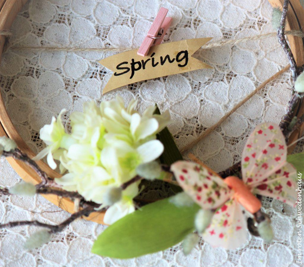 """Stickrahmen verziert mit Weidenkätzchen, Kunstblumen, einem kleinen Schmetterling und dem Schriftzug """"spring""""."""